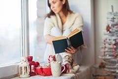 在圣诞节的富有思想的妇女阅读书装饰了得在家 图库摄影
