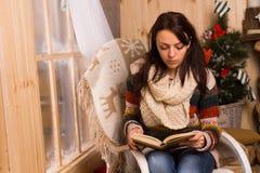 在圣诞节的少妇坐的读书 图库摄影