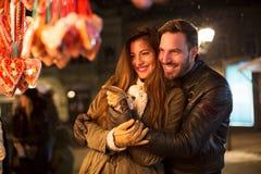 在圣诞节的微笑的年轻夫妇购物时间 库存照片