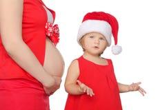 在圣诞节的惊奇的儿童和孕妇腹部 免版税库存照片