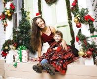 在圣诞节的愉快的家庭在等待gests和微笑的红色帽子 库存照片