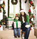 在圣诞节的愉快的家庭在红色帽子 免版税库存图片
