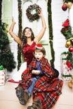 在圣诞节的愉快的家庭在红色帽子 免版税图库摄影