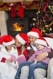 在圣诞节的愉快的家庭读书 图库摄影