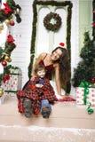 在圣诞节的愉快的微笑的家庭在有礼物、年轻母亲和小儿子的房子圣诞老人红色帽子的,生活方式假日 库存照片