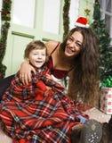 在圣诞节的愉快的微笑的家庭在有礼物、年轻母亲和小儿子的房子圣诞老人红色帽子的,生活方式假日 免版税库存照片