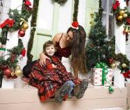 在圣诞节的愉快的微笑的家庭在有礼物、年轻母亲和小儿子的房子圣诞老人红色帽子的,生活方式假日 图库摄影