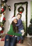在圣诞节的愉快的微笑的家庭在有礼物、年轻母亲和小儿子的房子圣诞老人红色帽子的,生活方式假日 免版税库存图片