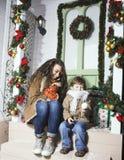 在圣诞节的愉快的微笑的家庭在有礼物的房子,年轻mot 免版税库存图片