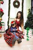 在圣诞节的愉快的微笑的家庭在有礼物的房子,年轻mot 库存照片
