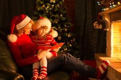 在圣诞节的愉快的母亲和儿童阅读书 库存照片
