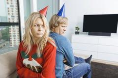 在圣诞节的毛线衣和紧接坐党的帽子的懊恼夫妇在家 免版税库存照片