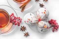 在圣诞节的热的茶在有茶树的玻璃透明以雪人的形式杯和蛋糕在蛋白甜饼,桂香外面 库存图片