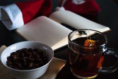 在圣诞节的计划未来:有空白页的一个笔记本,一支黑笔,圣诞老人帽子,有茶袋的,白色碗玻璃杯子巧克力 免版税库存图片