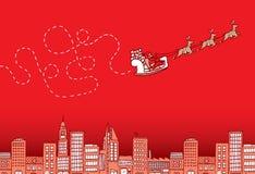 在圣诞节的迷茫的圣诞老人飞行在城市 免版税库存照片
