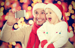 在圣诞节的Selfe 愉快的家庭爸爸有女儿的和拍摄在手机 免版税库存图片