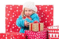 在圣诞节礼物盒附近的滑稽的小女孩 免版税库存照片