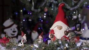 在圣诞节红色盖帽的神仙的地精在一棵圣诞树的背景与眨眼睛光的 圣诞节和新年构成 股票录像
