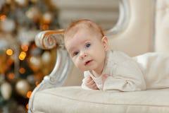 在圣诞节背景的一把椅子的小女孩婴孩  库存图片
