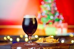 在圣诞节背景的冷的黑啤酒 库存照片