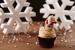 在圣诞节背景的圣诞老人杯形蛋糕 免版税图库摄影