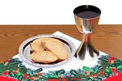 在圣诞节背景的银盘用面包和酒杯 免版税库存照片