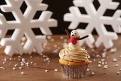 在圣诞节背景的雪人杯形蛋糕 免版税库存图片