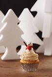 在圣诞节背景的雪花杯形蛋糕 库存照片