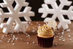 在圣诞节背景的雪花杯形蛋糕 免版税库存图片