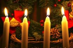 在圣诞节花圈前面的金黄蜡烛 免版税库存图片