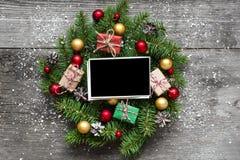 在圣诞节花圈的空白的照片框架与装饰和礼物盒在土气木桌上 图库摄影