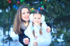 在圣诞节街道上的魔术  愉快的年轻母亲和女儿圣诞节时间的 库存照片