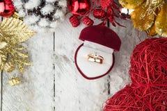 在圣诞节装饰中的婚戒在木背景 库存图片