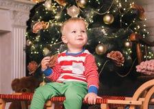 在圣诞节装饰中的愉快的儿童男孩在家 免版税图库摄影