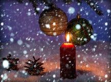 在圣诞节装饰和落的雪背景的红色蜡烛  库存图片