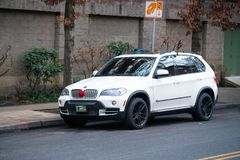 在圣诞节装饰品装饰的白色BMW 免版税库存照片