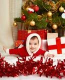 在圣诞节装饰的愉快的婴孩在毛皮的画象,谎言在杉树附近和礼物,寒假概念 免版税库存图片