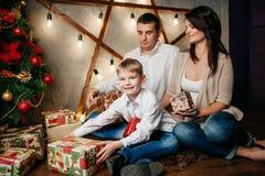在圣诞节装饰的愉快的年轻家庭 免版税库存图片