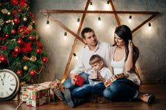 在圣诞节装饰的愉快的年轻家庭 库存照片