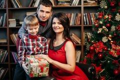 在圣诞节装饰的愉快的年轻家庭 库存图片