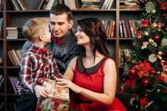 在圣诞节装饰的愉快的年轻家庭 免版税图库摄影