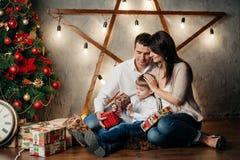 在圣诞节装饰的愉快的年轻家庭 免版税库存照片