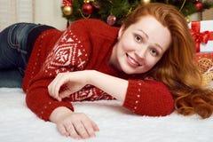在圣诞节装饰的美好的女孩谎言 家庭内部、杉树和礼物 除夕和寒假概念 免版税库存照片