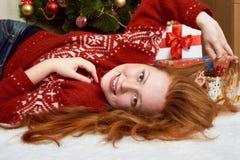 在圣诞节装饰的美好的女孩谎言 家庭内部、杉树和礼物 除夕和寒假概念 免版税库存图片