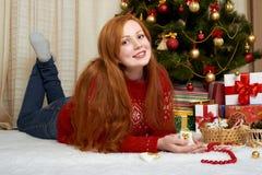 在圣诞节装饰的美好的女孩谎言 家庭内部、杉树和礼物 除夕和寒假概念 库存照片