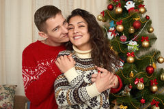 在圣诞节装饰的年轻夫妇 与礼物和杉树的家内部 新年假日概念 爱和柔软 图库摄影