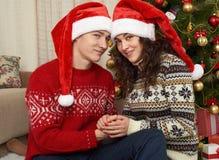 在圣诞节装饰的年轻夫妇 与礼物和杉树的家内部 新年假日概念 爱和柔软 免版税库存照片