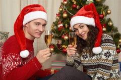 在圣诞节装饰的年轻夫妇 与礼物和杉树的家内部 新年假日概念 爱和柔软 免版税库存图片