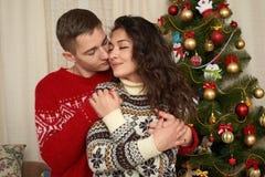 在圣诞节装饰的年轻夫妇 与礼物和杉树的家内部 新年假日概念 爱和柔软 库存图片
