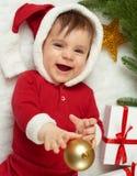 在圣诞节装饰的婴孩画象,穿戴作为圣诞老人,谎言在毛皮在杉树和戏剧与礼物,寒假概念附近 免版税库存照片